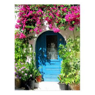Puerta azul enmarcada con el bougainvillea hermoso postal