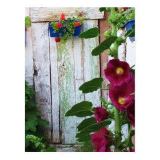 Puerta azul griega en jardín de flores en Grecia Postales
