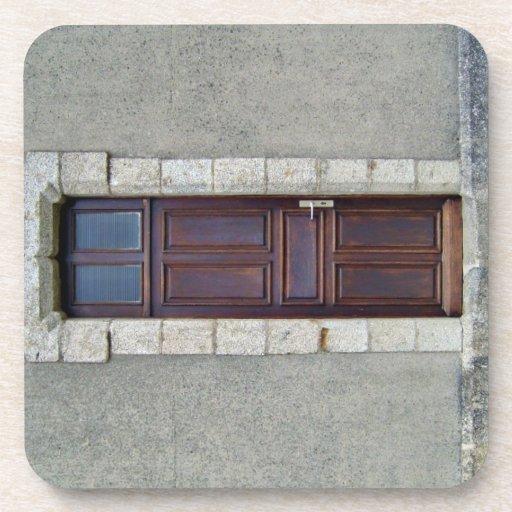Puerta de madera antigua en la pared de piedra posavasos