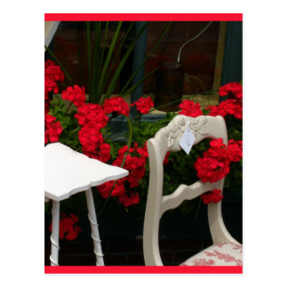 Puerta roja del blanco de los geranios tarjeta postal