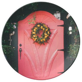 Puerta rosada adornada con las flores amarillas platos de cerámica