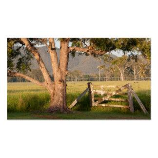 Puerta y árbol de la granja con las colinas tarjetas de visita