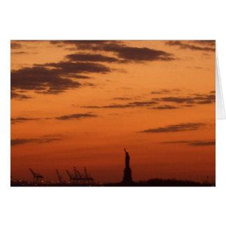 Puerto de Nueva York de la puesta del sol y estatu Tarjeton
