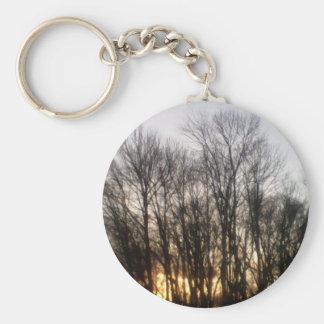 Puesta del sol a través de árboles llaveros personalizados
