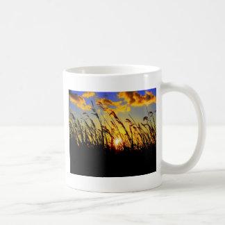 puesta del sol a través de la hierba larga tazas