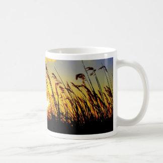 puesta del sol a través de la hierba larga taza de café