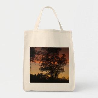 Puesta del sol a través de los árboles bolsa de mano