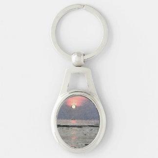 Puesta del sol acuosa llavero plateado ovalado