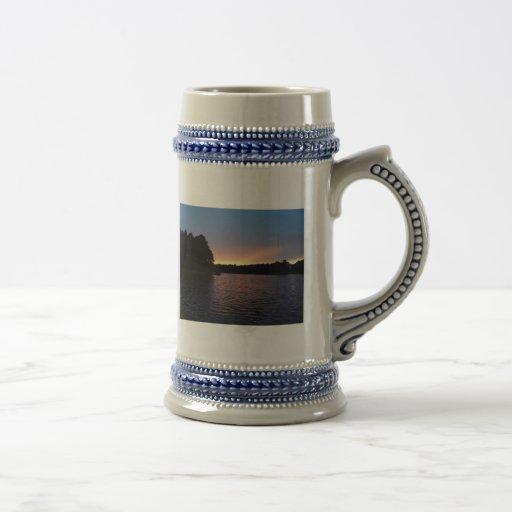 Puesta del sol amelocotonada sobre el cisne del la taza de café