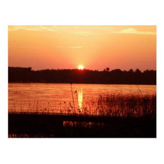 Puesta del sol anaranjada en el lago postal