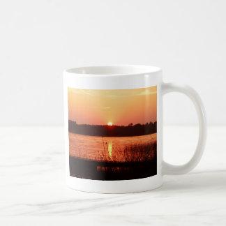 Puesta del sol anaranjada en el lago taza