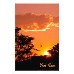 Puesta del sol anaranjada preciosa con las silueta  papeleria