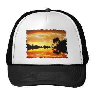 Puesta del sol anaranjada reflejada en los árboles gorras de camionero