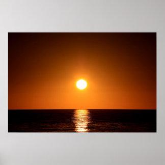 Puesta del sol anaranjado oscuro con la reflexión poster