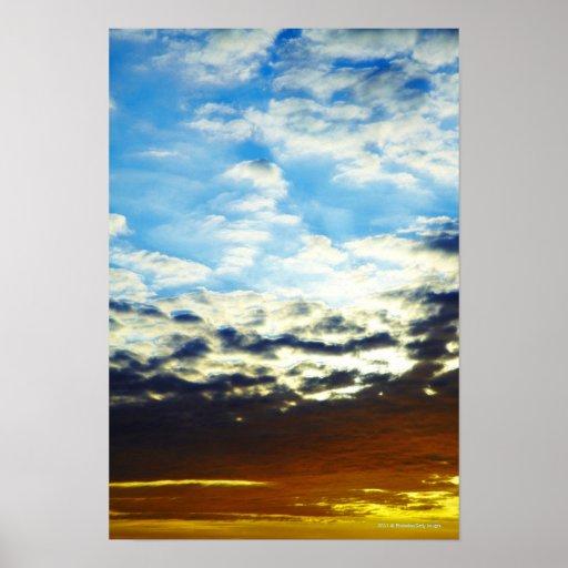 Puesta del sol azul anaranjada roja con las nubes póster