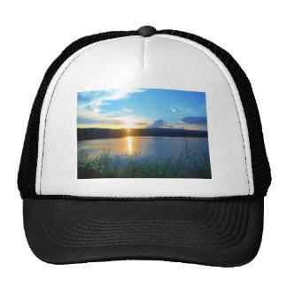 Puesta del sol azul en el lago gorras