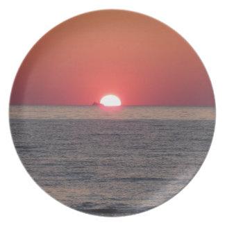 Puesta del sol caliente del mar con el buque de plato de cena