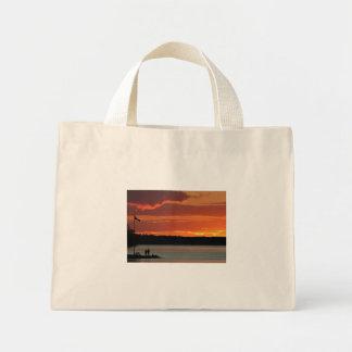 Puesta del sol clara del lago bolsas de mano