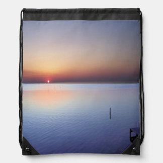 Puesta del sol colorida de la playa mochilas