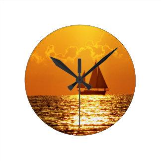Puesta del sol con el barco relojes de pared