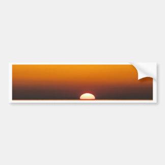 Puesta del sol con el pescador en la orilla del etiqueta de parachoque