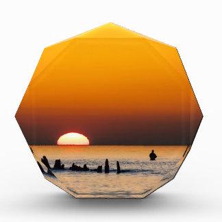 Puesta del sol con el pescador en la orilla del ma