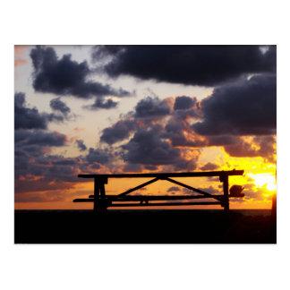 Puesta del sol con la mesa de picnic tarjeta postal