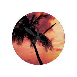 Puesta del sol con la palma relojes
