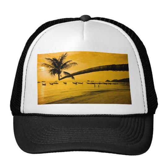 Puesta del sol con la palma y los barcos en la pla gorros