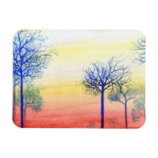 Puesta del sol con los árboles azules imán