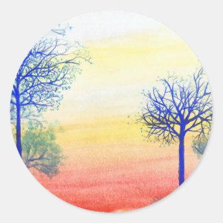 Puesta del sol con los árboles azules pegatina redonda