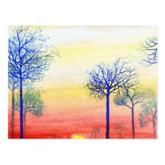 Puesta del sol con los árboles azules postal