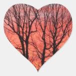 Puesta del sol contra los árboles pegatina en forma de corazón