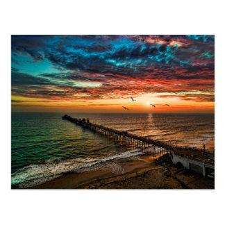 Puesta del sol de la costa postales