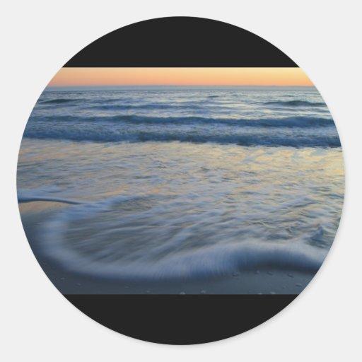 puesta del sol de la playa y acción de la onda pegatina redonda