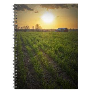 Puesta del sol de las tierras de labrantío cuadernos