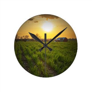 Puesta del sol de las tierras de labrantío reloj redondo mediano