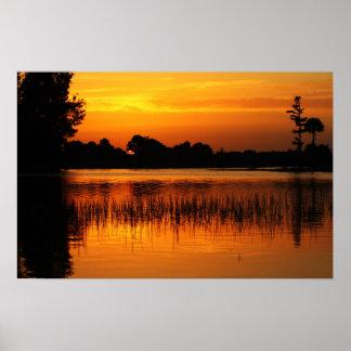 Puesta del sol de oro detrás de un lago poster