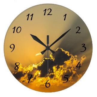 Puesta del sol de oro que ilumina una nube reloj redondo grande