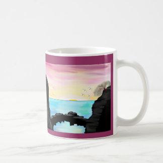 Puesta del sol de una cueva del mar tazas de café