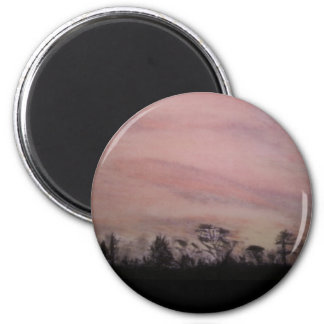 Puesta del sol del carbón de leña sobre árboles imán redondo 5 cm