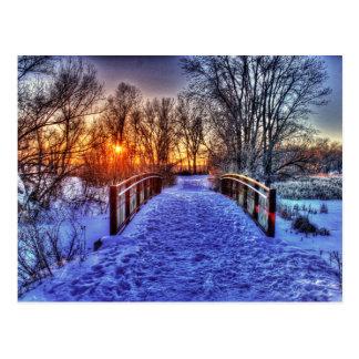Puesta del sol del invierno en el puente postales