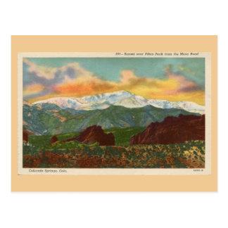 Puesta del sol del vintage sobre el pico de los postal