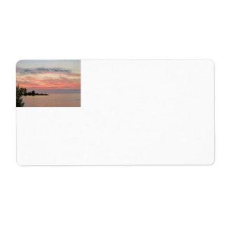 Puesta del sol detrás de las nubes por el lago etiquetas de envío