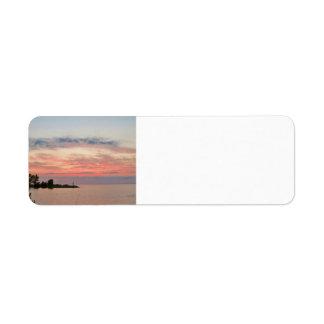 Puesta del sol detrás de las nubes por el lago etiqueta de remite