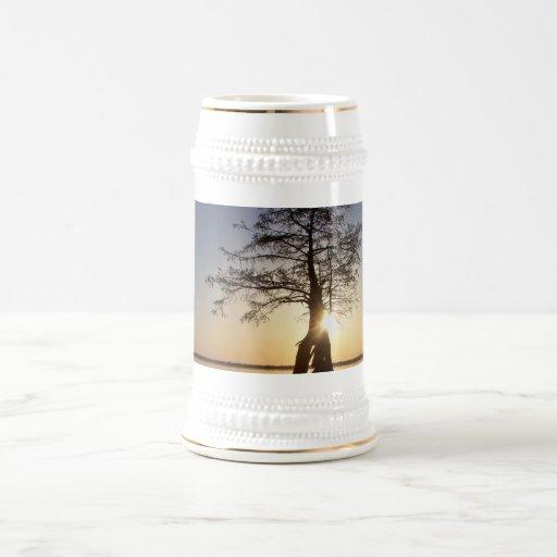 Puesta del sol detrás de un árbol tazas de café