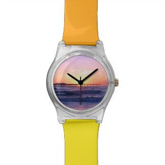 Puesta del sol detrás de un embarcadero reloj