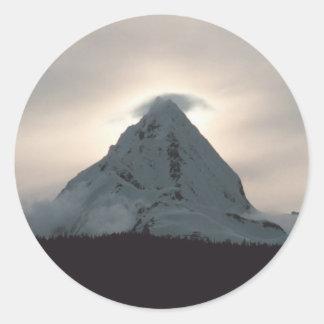 Puesta del sol detrás de una montaña nevosa etiqueta redonda