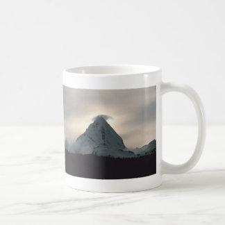 Puesta del sol detrás de una montaña nevosa tazas de café