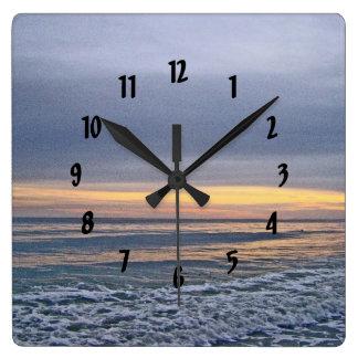 Puesta del sol divina a lo largo de la playa de la relojes de pared